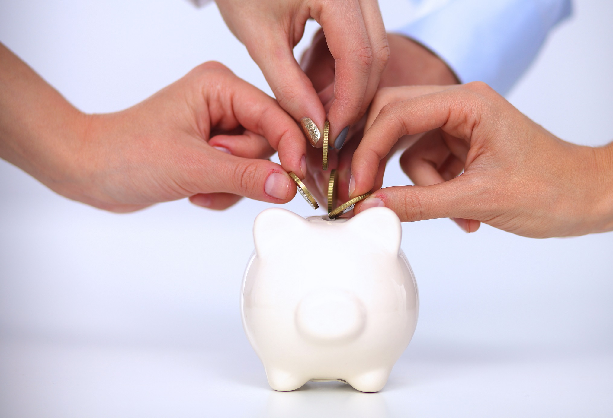 People putting coin into the piggy bank, isolated o white background
